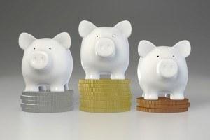 Sparschweine stehen auf Siegerpodest aus Geldstücken